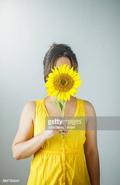 Woman hiding her face behind a sunflower.