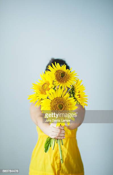 Woman hiding her face behind sunflowers.