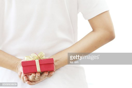 woman hiding red gift box behind her back : Stock Photo