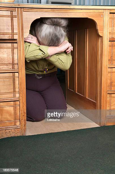 Frau versteckt unter einem Schreibtisch
