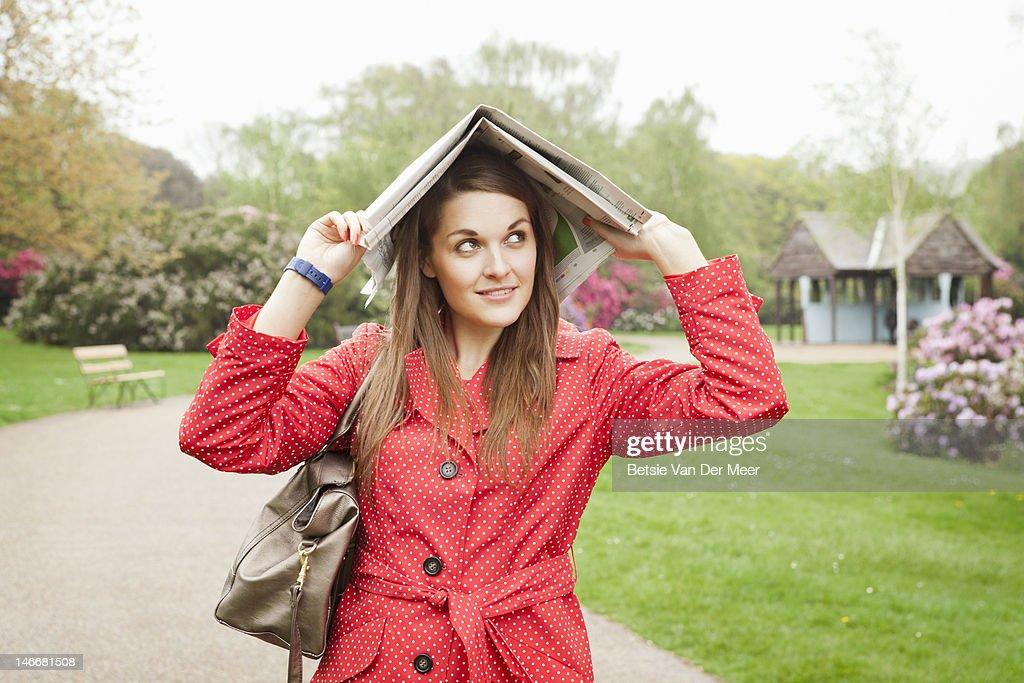 Woman hiding under newspaper for rain.