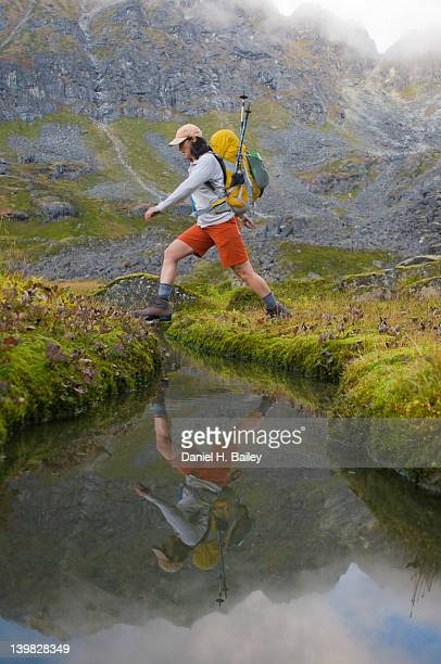Woman hiker, 40s, wearing a backpack, stepping over a small mountain pond, reflecting in the water, Talkeetna Mountains, Alaska