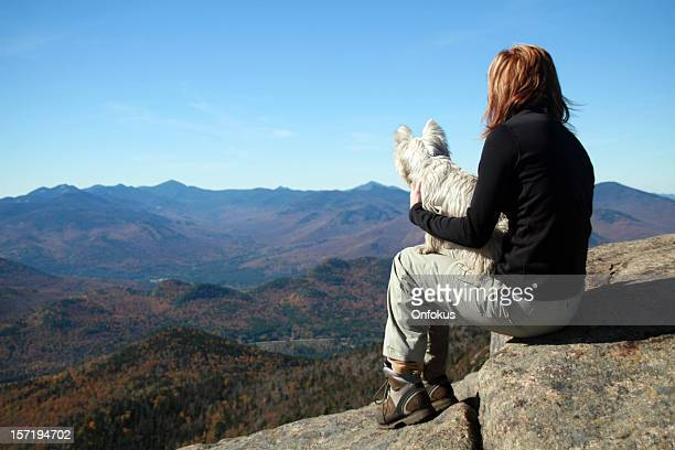 Woman hiking and holding westie dog on a mountain summit
