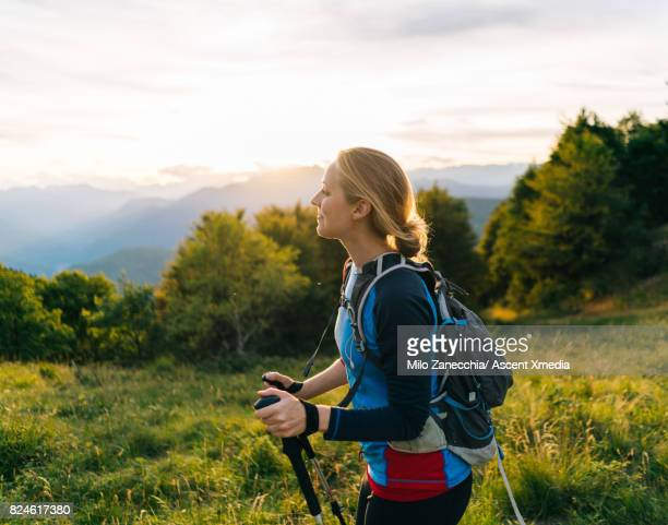 Woman hikes along trail at sunrise, mountains