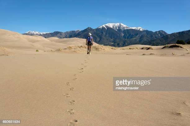 Woman hikes Great Sand Dunes National Park Sangre de Cristo Mountains Colorado