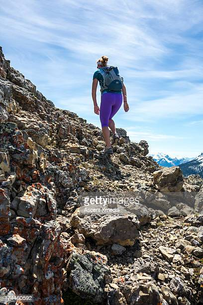 Woman hikes through rocks towards mtn summit