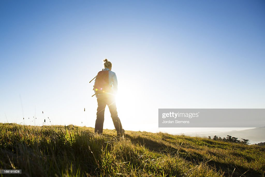 A woman hiking above the ocean. : Stock Photo