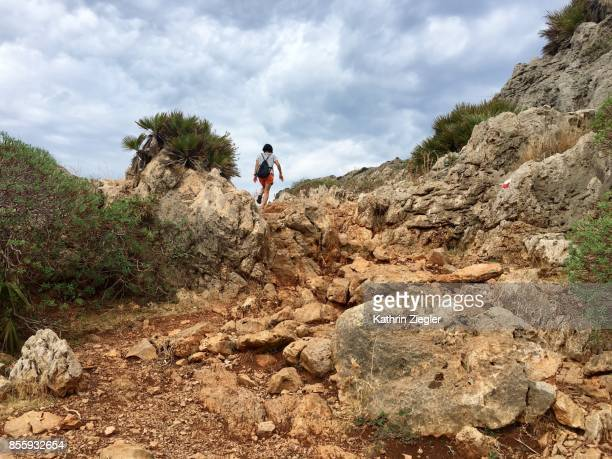 Woman hiking alone on rocky dirt road, Sicily