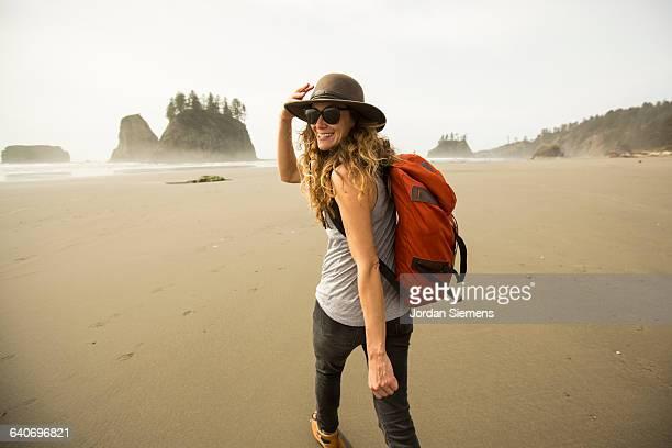 A woman hiking along a remote beach.