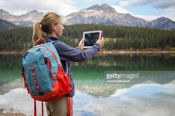 Femme de randonnée par le lac permet de photo à l'aide de tablette numérique