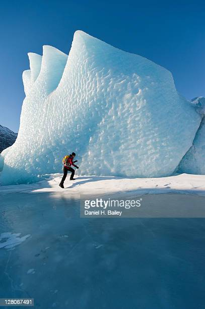 Woman hiking in front of an ice formation on the Knik Glacier, winter, Chugach Mountains, Alaska, USA, March 2011