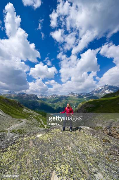 A woman hiking in mountains and lakes stops to take in the view.