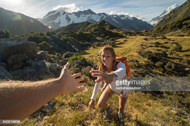 Woman hiking pulls out hand to get assistance from teammate