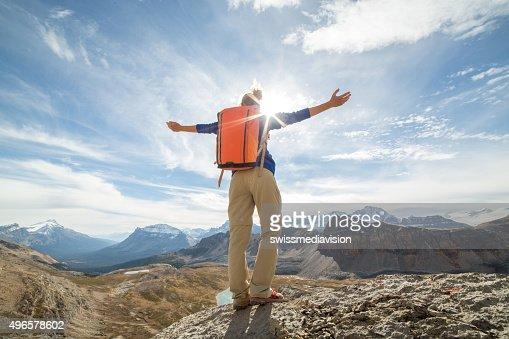 Woman hiking reaches mountain top, arms outstretched