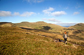 Wanderlust and healthy lifestyle concept. Attractive young woman hiking across a mountain ridge towards Pen y Fan with a rugged landscape and blue sky. Pen y Fan is the highest peak in south Wales at