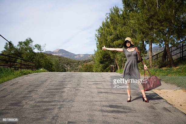 Woman hitchhiking on rural road