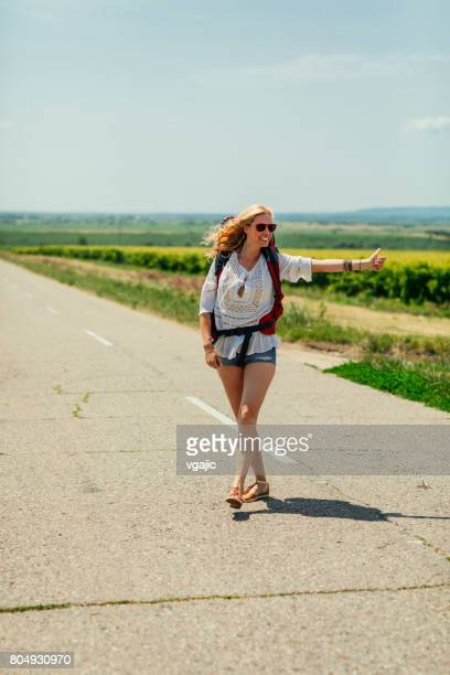 Woman hitchhiking on the road trip
