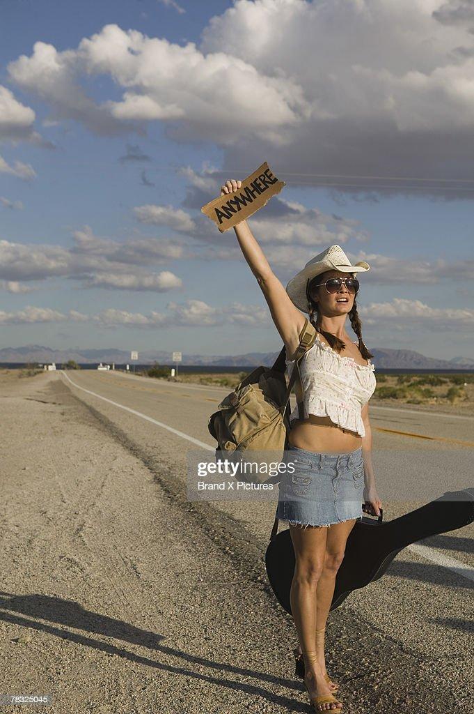 Woman hitchhiking : Stock Photo