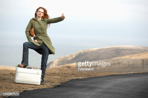 Woman hitchhiking with metal briefcase