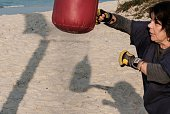A woman hits a sandbag as she trains beach boxing at Pepe beach in Rio de Janeiro Brazil on July 26 2016 Since boxing trainer Moacyr Lima first...