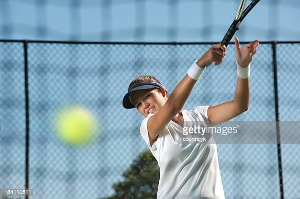 Femme frapper la balle de tennis