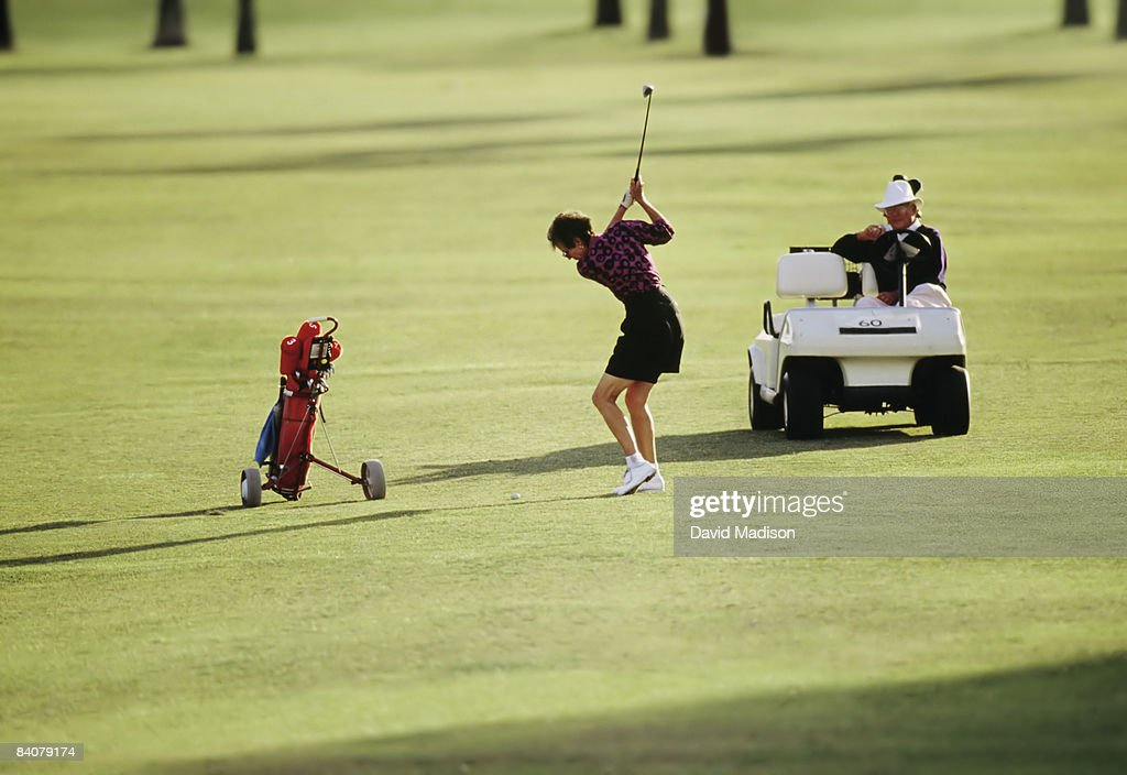Woman hitting golf drive with instructor watching : Stock Photo
