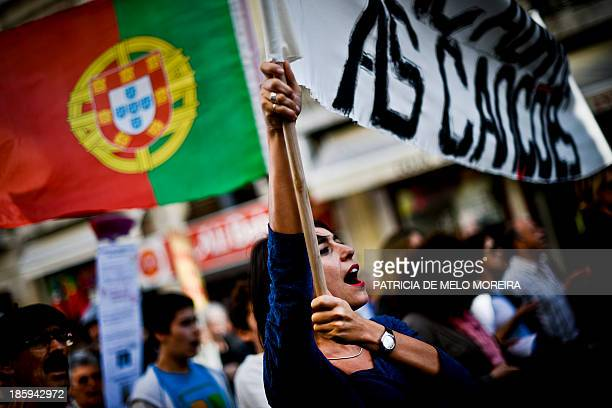A woman hold a banner during the demonstration 'Damn the Troika' against the government austerity policies in downtown Lisbon on October 26 2013 Last...