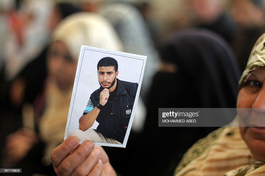 A woman hold a photo of a relative being held in an Israel jails during a protest in front of the Red Cross offices in Gaza City on April 22, 2013. According to Israeli rights group B'Tselem some 4,713 Palestinians are being held in Israeli facilities.