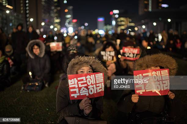 TOPSHOT A woman hold a placard reading 'Arrest Park GeunHye' during a small rally following the impeachment of President Park GeunHye in central...