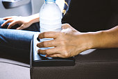 Woman hand hold drinking water bottle on cup holder in car