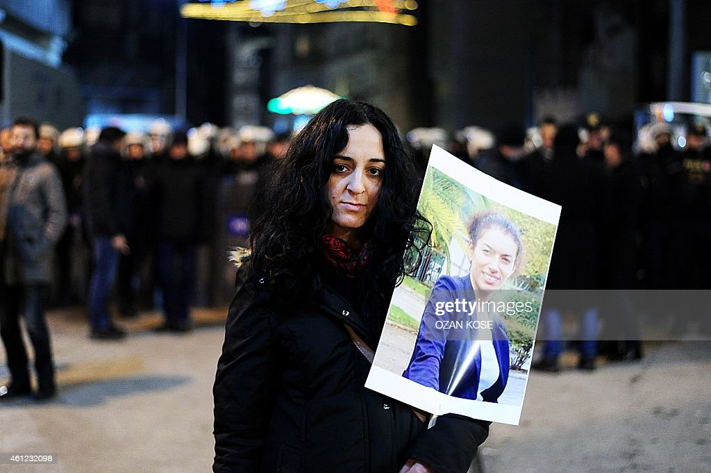 A woman hold picture of killed kurdish activist Fidan Dogan front of a police barricade during a demonstration on January 9, 2015 at Istiklal avenue in Istanbul to commemorate the killing of the three top Kurdish activists <a gi-track='captionPersonalityLinkClicked' href=/galleries/search?phrase=Sakine+Cansiz&family=editorial&specificpeople=10112049 ng-click='$event.stopPropagation()'>Sakine Cansiz</a>, Fidan Dogan and Leyla Soylemez. The three women were shot to death on January 9, 2013 at the Kurdish Information Centre in Paris.The motives of the triple killing remain unclear. Banner reads: '365 days later, we are still waiting for the truth. Find those responsible'. AFP PHOTO/OZAN KOSE