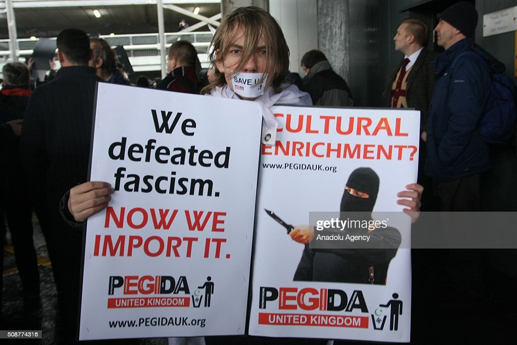 A woman hold placards during the 'silent march' organized by Pegida (Patriotic Europeans against the Islamisation of the West) UK supporters in Birmingham, England on February 6, 2016.