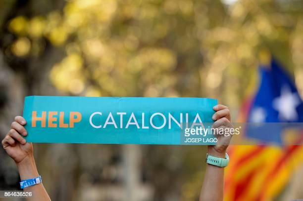 A woman hold placards reading 'Help Catalonia' during a demonstration on October 21 2017 in Barcelona to support two leaders of Catalan separatist...