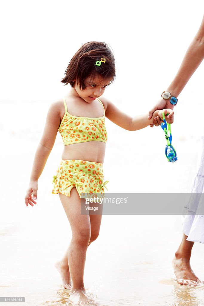 Woman Holding A Baby Girls Hand Walking At A Beachside ...
