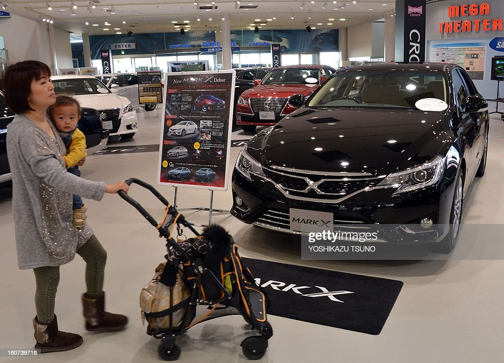 A woman holding a baby looks at Toyota Motor vehicles at the company's showroom in Tokyo on February 5, 2013. Toyota said its net profit quadrupled for the nine months to December as the Japanese auto giant revised upward its full-year profit and sales forecast. AFP PHOTO / Yoshikazu TSUNO