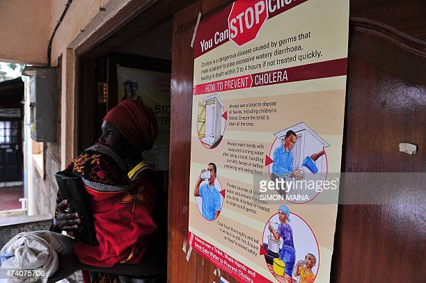 A woman holding a baby walks past a poster with information about cholera at a hospital in the Kibera area of Nairobi on May 20 2015 At least 65...