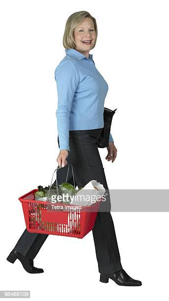 A woman holding a basket of groceries
