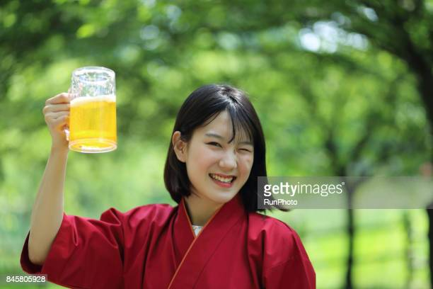 woman holding a beer glass winking a chef