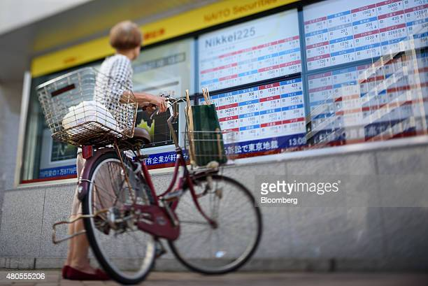 A woman holding a bicycle looks at an electronic stock board outside a security firm in this photograph taken with a tiltshift lens in the Ginza...