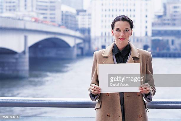 Woman holding a blank piece of paper