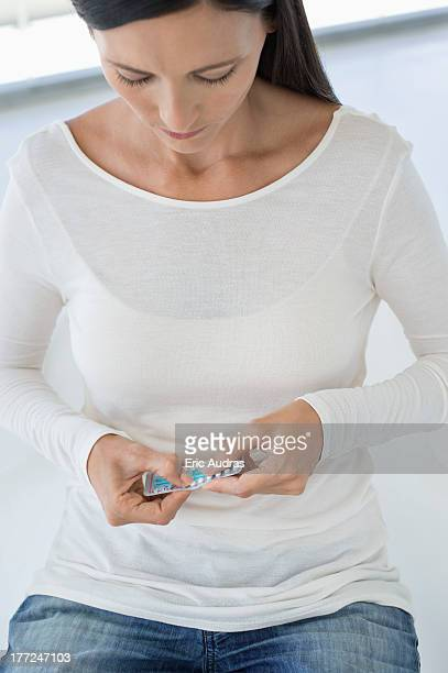 Woman holding a blister pack of contraceptive pills
