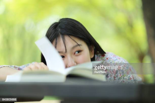 woman holding a book on a park table and looking at the left