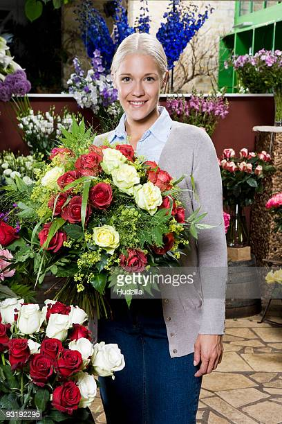 A woman holding a bouquet of roses in a florists