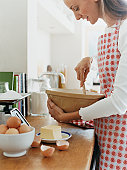 Woman Holding a Bowl and a Wooden Spoon in a Kitchen