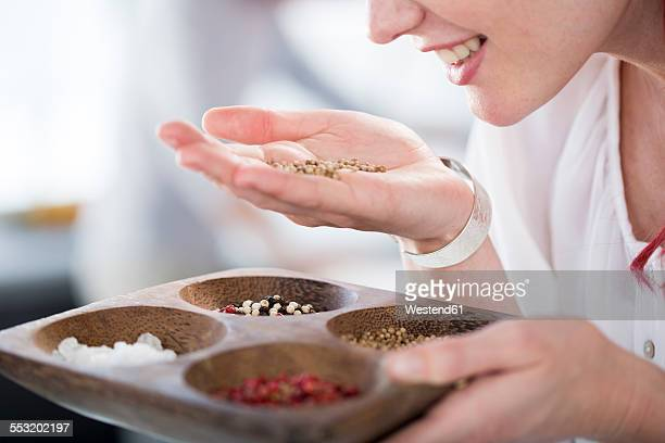 Woman holding a bowl and smelling spices