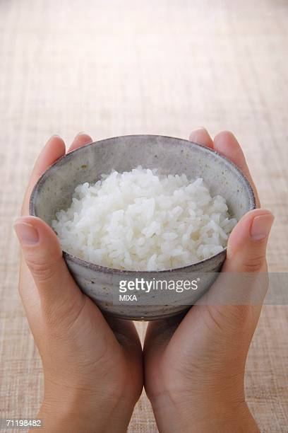 A woman holding a bowl of rice