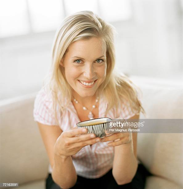 Woman holding a bowl with soup.