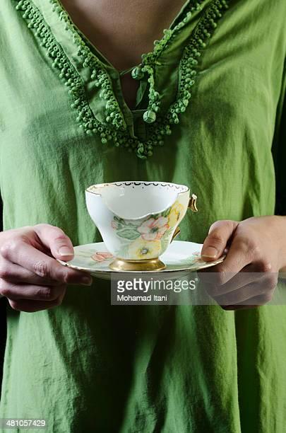 Woman holding a broken teacup