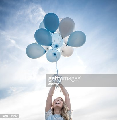 Woman holding a bunch of helium balloons outdoors