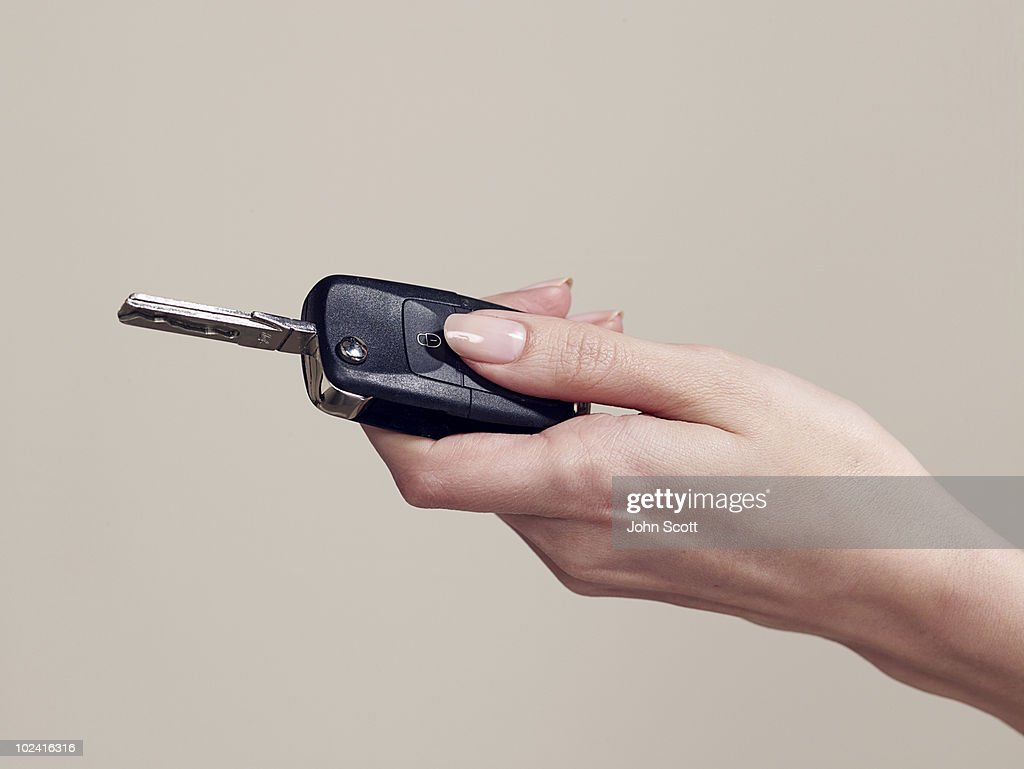Woman holding a car key, close-up of hand : Stock Photo